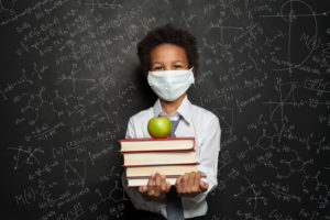 School boy wearing a mask and holding school books and an apple in front of a chalk board