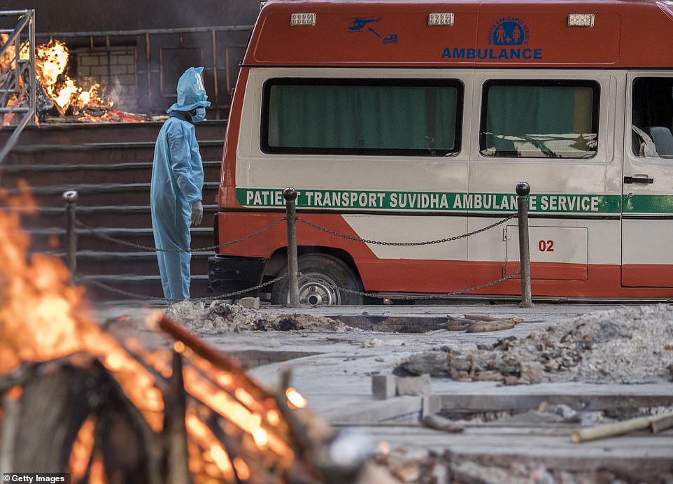 A man wearing PPE waits to transfer the body of his relative who died of the Covid-19 coronavirus infection from an ambulance amid burning pyres of other covid deaths at a crematorium in Delhi on April 17