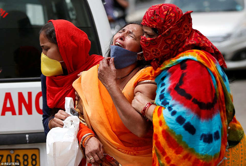 A woman is consoled after her husband died due to Covid outside a mortuary of a COVID-19 hospital in Ahmedabad