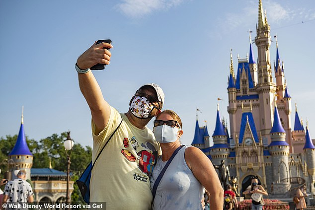 Last month, the CDC said 'less than 10%' of all coronavirus transmission is occurring outdoors. Pictured: Guests stop to take a selfie at Magic Kingdom Park at Walt Disney World Resort, July 2020