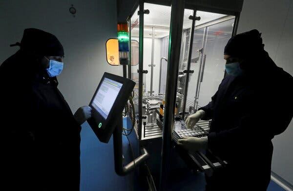 Laboratory technicians work on production of remdesivir, an antiviral drug.